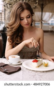fashion  photo of gorgeous woman with dark curly hair in luxurious sequin dress, eating dessert in cafe