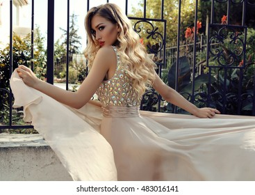 fashion photo of gorgeous young woman with blond curly hair and bright makeup, in luxurious sequin dress posing outdoor