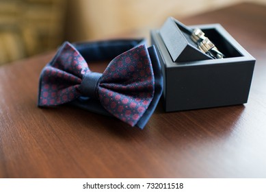 Fashion photo of a man with beard correcting his bowtie, Classic groom accessories