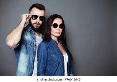 Fashion photo of a modern stylish beautiful couple in casual clothes and sun glasses