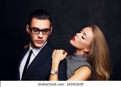 Fashion photo of office romance of sexy lovers,pretty blond woman with watch,red lipstick,and handsome brunette businessman wearing in suit,tie,glasses,they are hugging and kissing on Valentine's day
