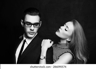 Fashion photo of office romance of sexy young lovers of beautiful blond woman and handsome brunette businessman wearing in format suit,tie,glasses, they are hugging and kissing on Valentine's day