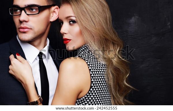 セクシーな恋人のオフィスロマンスのファッション写真、時計と綺麗な金髪の女性、赤い口紅、スーツ、ネクタイ、眼鏡をかけたハンサムなブルネットのビジネスマン、バレンタインデーに抱き合ったりキスをしたりする