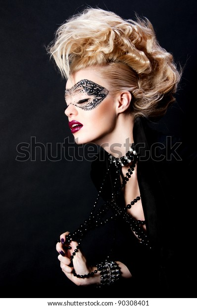 fashion photo of pretty blond woman with mask on face and creative hairstyle