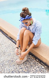 Fashion photo of sexy beautiful Girl in plaid shirt and sunglasses relaxing beside a swimming pool. Outdoors lifestyle  portrait