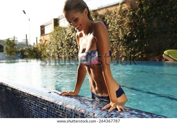 fashion photo of sexy beautiful girl with blond hair in elegant bikini relaxing in swimming pool