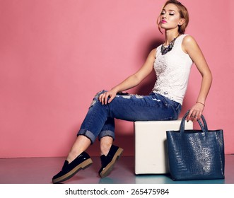 Fashion photo of sexy beautiful woman with blond curly hairstyle wearing a  blue jeans,white top,black shoes and jewelry holding a bag and posing on a chair