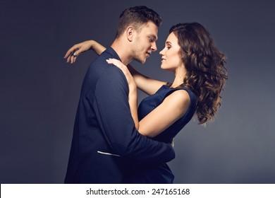 Fashion photo of sexy elegant couple in the tender passion. Studio portrait