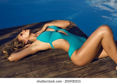 fashion photo of sexy glamour model with long blond hair in blue swimsuit relaxing beside a swimming pool