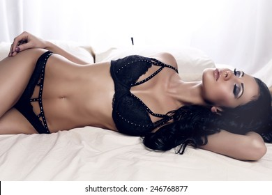 fashion photo of sexy glamour woman with dark hair wearing elegant black lingerie lying on bed in bedroom