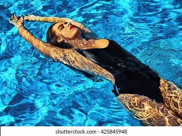 fashion photo of sexy hot beautiful girl model with dark hair in black swimwear swimming on back in swimming pool with red lips