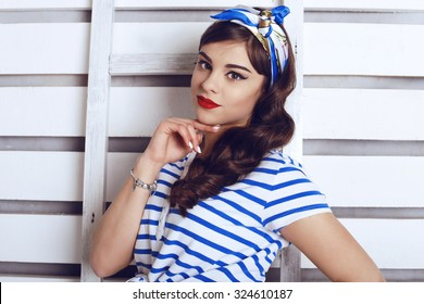 Fashion photo of sexy young brunet pin-up girl with beautiful eyes and full red lips,curly hair and stylish headband wearing in the blue stripes top and posing with ladder against white boards