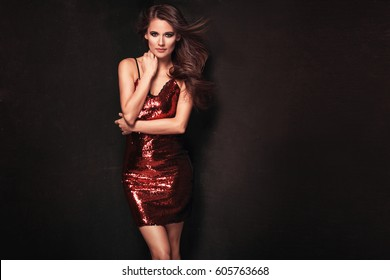 Fashion photo of a stunning brunette woman in luxurious glitter red dress. Sexy party body