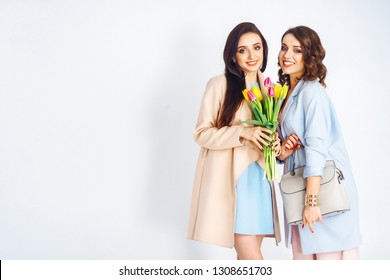 Fashion photo of two beautiful young women with tulips in the hand .they  dressed in a beautiful coat, and T-shirt with stripes.Spring concept.March 8. beautiful girls in stylish clothes