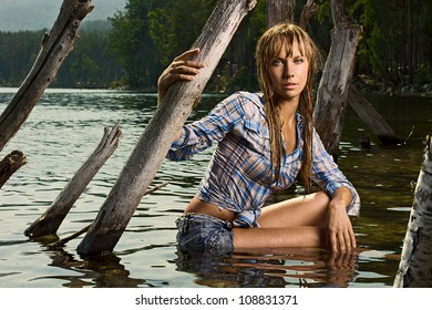 Fashion photo of young beautiful woman sitting in the water and looking at camera? her hair are wet