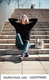 Fashion photo of a young beautiful woman in jeans, a black sweatshirt, a white knitted hat with a backpack in her showlder sitting on the steps of a stone staircase outside