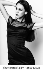 Fashion photo of young elegant woman on white background. Girl posing. Studio photo. Black and White image