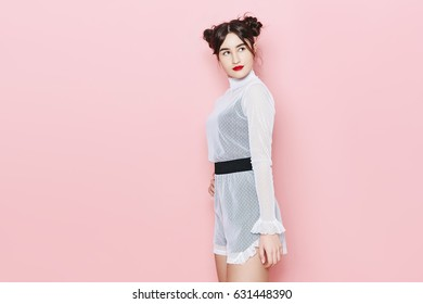 7ca5e94de37 Fashion photo of young girl posing over pink background in studio