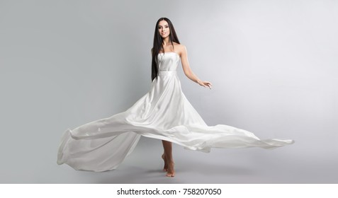 fashion photo of young girl in white dress flying tissue. Lightweight material. Grey background