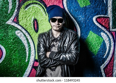 Fashion photo of young guy posing on bright wall