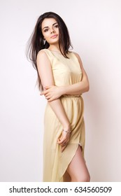 Fashion photo of young magnificent woman dressed in a beige dress on white background. Girl posing. Studio photo.