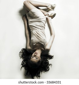 Fashion photo. Young seductive woman lays on white bedsheet