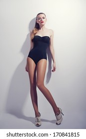 Fashion photo of young sexy and beautiful woman in swimsuit and high heel shoes
