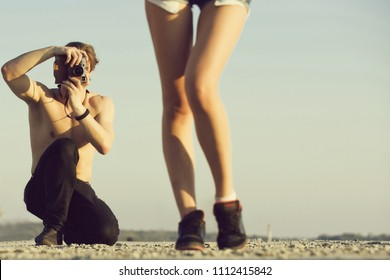 Fashion photographer. Caucasian man, sexy macho or handsome photographer with naked torso shooting pretty female legs on retro camera on sunny day on blue sky. Photoshoot on nature. Summer vacation