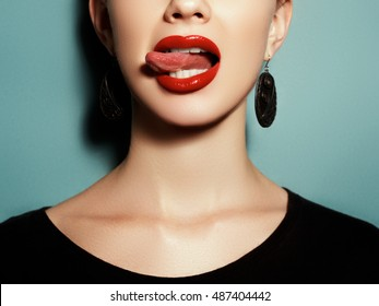 Fashion photography. Portrait. A model with one earring on a colorful background. Natural full lips with bright lip makeup. Red lipstick and lip gloss