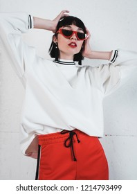 fashion photography. Stylish girl model in red trousers and a white sweatshirt. Studio photography.