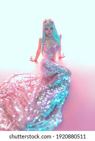 Fashion photography. Young model posing in studio in beautiful pink dress