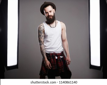 Fashion Photosession of Handsome Bearded Man in Hat. Brutal hipster boy with tattoo posing in a photo studio