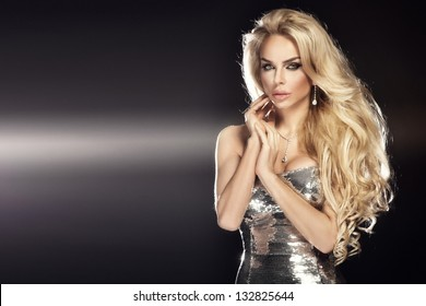 af1bdea84e4 Fashion picture of beautiful young blonde woman wearing glitter silver dress.  Long healthy curly hair