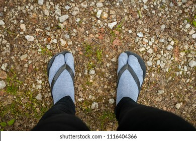 Fashion police victim - wearing sandals over feet covered with gray socks. Terrible thing to do. Grey socks in brown thong slippers, looking from above. Feet on stone and dirt surface.