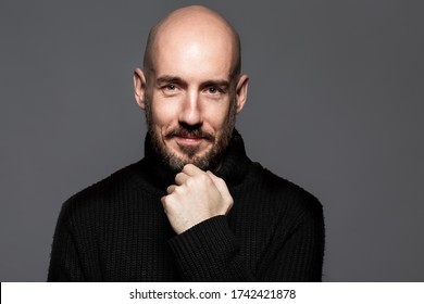 Fashion Portrait of a 40-year-old man standing over a light gray background in a black sweater. Close up. Classic style. Bald shaved head. Copy-space. Studio shot