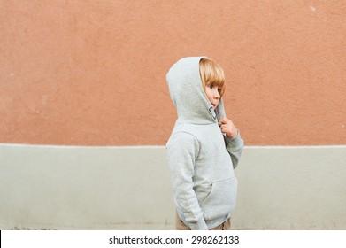 Fashion portrait of adorable toddler boy wearing grey sweatshirt