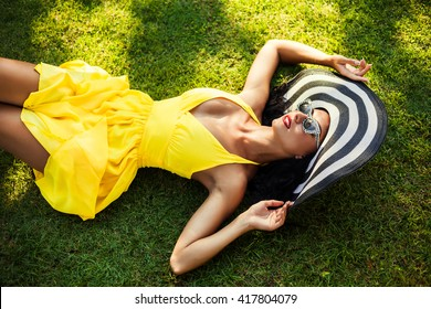 Fashion portrait of amazing girls, lady lying on green grass in a bright yellow dress in a luxurious wide striped hat, retro sunglasses, sensual glamour, makeup with red lips clean healthy skin face