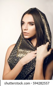 Fashion portrait of androgynous beautiful man with perfect glossy long hair wearing arabian style black golden cloth. Glamour feminine attractive model with arabian evening make-up. Isolated on white