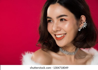 Fashion portrait of Asian Black hair tanned skin woman with strong super color red lips wearing white fur Diamond earrings necklace, studio lighting red reddish background copy space text logo