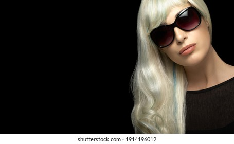 Fashion portrait of an attractive blond woman with healthy long silver white hair, wearing black sunglasses, looking at camera. Close-up isolated on black background with copy space for text