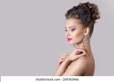 fashion portrait of a beautiful attractive girl with a gentle elegant evening wedding hairstyles high and bright make-up , with flowers in their hair and large earrings