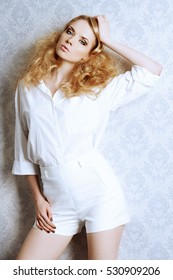 Fashion portrait of a beautiful blonde woman in white blouse and shorts posing by a classic vintage wallpaper. Vogue shot. Hairstyle, make-up.