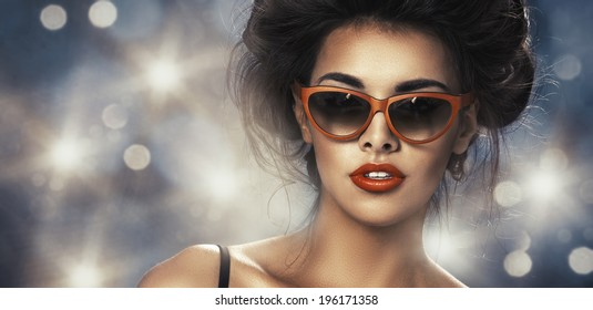Fashion portrait of a beautiful brunette woman with shot hairstyle with orange sunglasses - studio photo