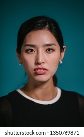 A fashion portrait of a beautiful, elegant and stylish Korean Asian woman in a black outfit against a blue background in a studio. She looks intelligent, confident and is gazing at the camera.