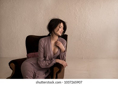 Fashion portrait of a beautiful girl in a dress sitting in the armchair. Deep Decollete. Large breasts. Round buttocks. Beige background. Brown Armchair.