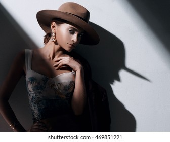 fashion portrait of beautiful girl in hat leaning the wall . studio location near the white wall with dark shadow.