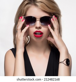 Fashion portrait of beautiful girl in sunglasses with red lips