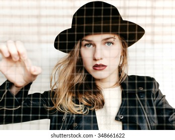Fashion portrait of beautiful girl wearing hat looking through the net and trapped inside cage trying to get out. Close-up of cute woman on white grid background not isolated.