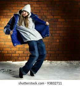 Fashion portrait of beautiful hip-hop woman dancing before bright brick wall