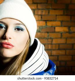 Fashion portrait of beautiful hip-hop woman posing on bright brick wall